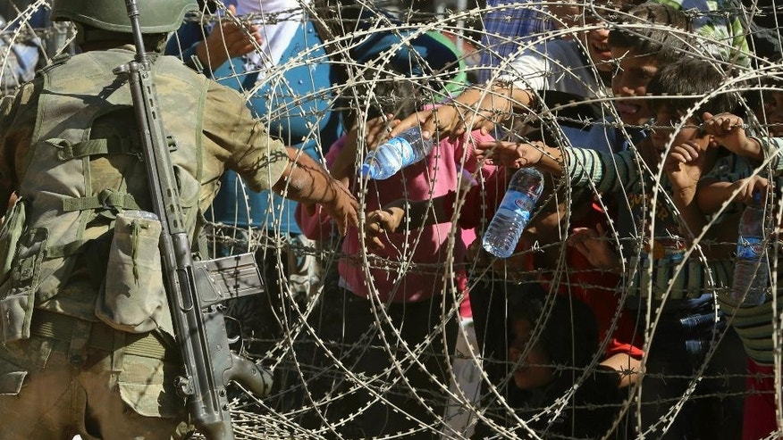 A Turkish soldier throws bottles of water toward  Syrian refugees waiting at the border in Suruc, Turkey, Sunday, Sept. 21, 2014. Turkey opened its border Saturday to allow in up to 60,000 people who massed on the Turkey-Syria border, fleeing the Islamic militants' advance on Kobani.  (AP Photo/Burhan Ozbilici)