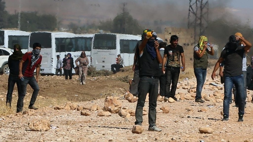 Kurdish demonsrators clash with Turkish security forces as thousands of Syrian refugees continue to arrive at the border in Suruc, Turkey, Monday, Sept. 22, 2014. Turkey opened its border Saturday to allow in up to 60,000 people who massed on the Turkey-Syria border, fleeing the Islamic militants' advance on Kobani.(AP Photo/Burhan Ozbilici)