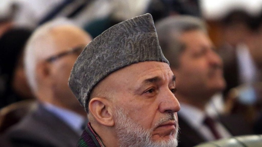 Afghan President Hamid Karzai attends his farewell ceremony at the presidential palace in Kabul, Afghanistan, Tuesday, Sept. 23, 2014. Outgoing President Karzai is taking one last swipe at the U.S., saying that America hasn't wanted peace in Afghanistan. Karzai on Tuesday said that peace will come to Afghanistan if the United States and Pakistan really want it. (AP Photo/Rahmat Gul)