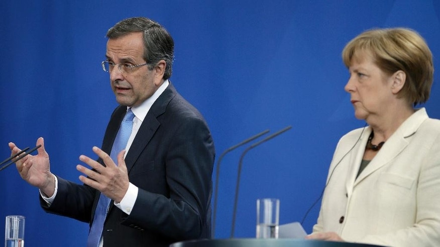 German Chancellor Angela Merkel, right, and Prime Minister of Greece Andonis Samaras, left, address the media during a joint press conference as part of a meeting at the chancellery in Berlin, Germany, Tuesday, Sept. 23, 2014. (AP Photo/Michael Sohn)