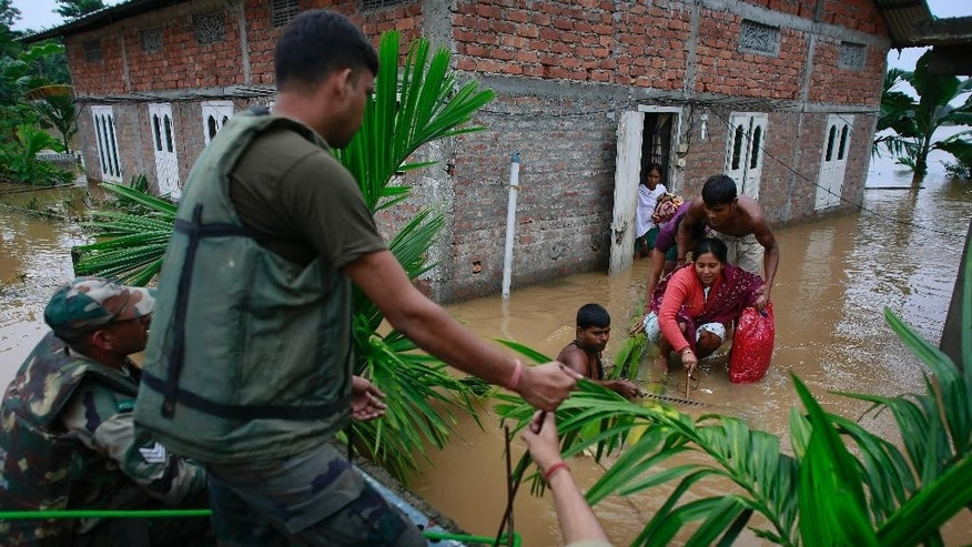 Indian army soldiers rescue flood-affected villagers at the Chaygaon village in Kamrup district of northeastern Assam state, India, Tuesday, Sept. 23, 2014. Landslides and flash floods triggered by two days of heavy rain have killed at least 28 people in India's remote northeast, officials said Tuesday. (AP Photo/Anupam Nath)