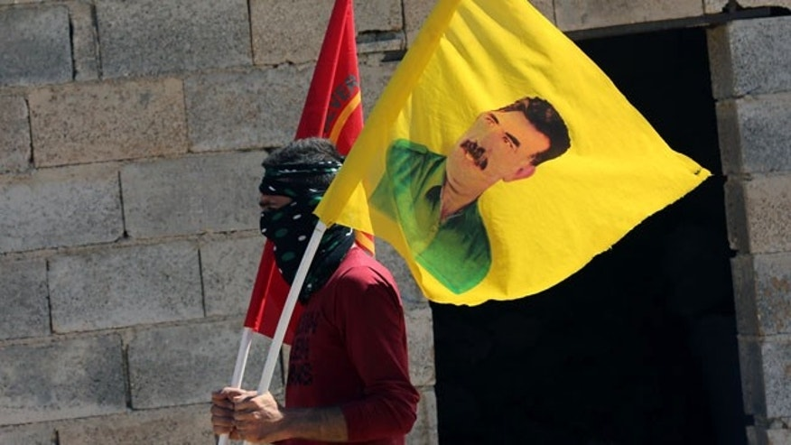 September 21, 2014: A masked protester waves a poster of jailed Kurdish rebel leader Abdullah Ocalan, amid a clash with security forces while several hundred Syrian refugees waited at the border in Suruc, Turkey. (AP Photo/Burhan Ozbilici)