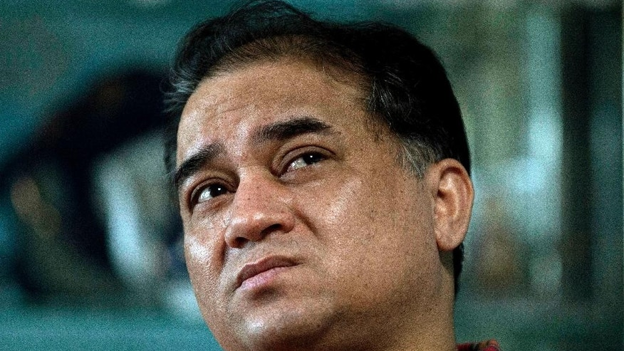In this Feb. 4, 2013 photo, Ilham Tohti, an outspoken scholar of China's Uighur minority, pauses during an interview at his home in Beijing, China. A Chinese court on Tuesday, Sept. 23, 2014 imposed a harsh life sentence on Ilham Tohti, who championed the country's Uighur minority, the most severe penalty in a decade for anyone in China convicted of illegal political speech. (AP Photo/Andy Wong)