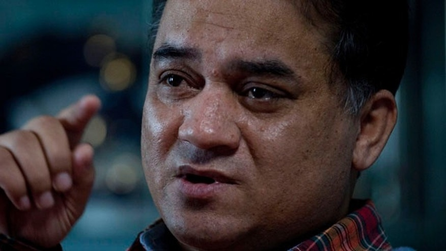 In this Feb. 4, 2013 photo, Ilham Tohti, an outspoken scholar of China's Turkic Uighur ethnic minority, speaks during an interview at his home in Beijing, China. (AP Photo/Andy Wong)