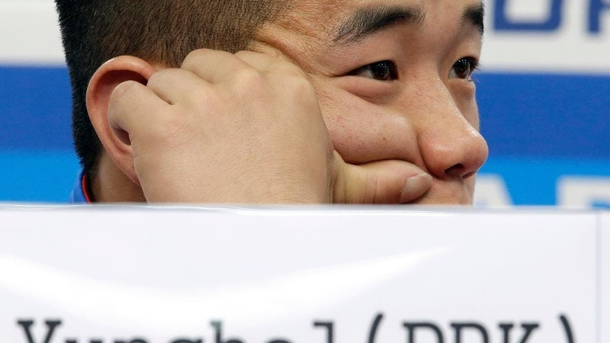 "North Korea's gold medalist Om Yun Chol listens to reporter's question during a press conference at the 17th Asian Games in Incheon, South Korea, Tuesday, Sept. 23, 2014. When the first world record fell at the Asian Games - to the North Korean weightlifter - elated South Korean fans pounded drums and stood to cheer. The media heaped congratulations on the athlete for winning the North's first gold medal. Away from the stadiums, however, South Korean activists were launching balloons laden with anti-North Korea leaflets over the demilitarized zone and the North's state-run media was churning out tirades against the South's ""puppet"" rulers and their unforgivable crimes. (AP Photo/Lee Jin-man)"