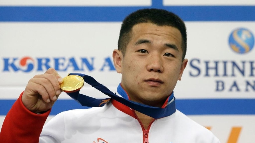 "North Korea's gold medalist of the Men's 56kg weightlifting Om Yun Chol poses with his gold medal during a press conference at the 17th Asian Games in Incheon, South Korea, Tuesday, Sept. 23, 2014. When the first world record fell at the Asian Games - to the North Korean weightlifter - elated South Korean fans pounded drums and stood to cheer. The media heaped congratulations on the athlete for winning the North's first gold medal. Away from the stadiums, however, South Korean activists were launching balloons laden with anti-North Korea leaflets over the demilitarized zone and the North's state-run media was churning out tirades against the South's ""puppet"" rulers and their unforgivable crimes.  (AP Photo/Lee Jin-man)"