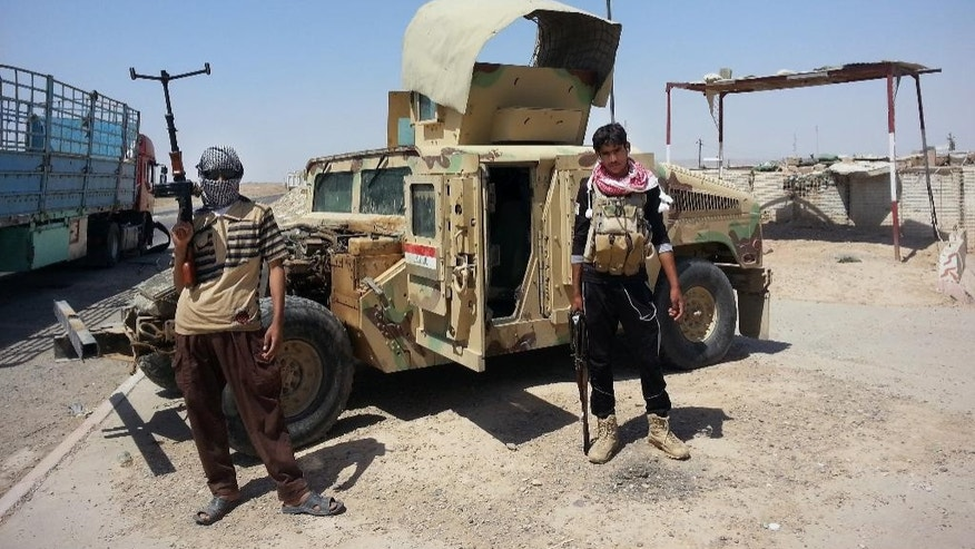 FILE - In this Thursday, June 19, 2014 file photo, Islamic State group militants stand with a captured Iraqi Army Humvee at a checkpoint outside Beiji refinery, some 250 kilometers (155 miles) north of Baghdad, Iraq.  The Syrian foreign ministry said Tuesday, Sept. 23, 2014 that Washington informed Damascus' envoy to the United Nations before launching airstrikes against the Islamic State group in Syria, attacks that activists said inflicted casualties among jihadi fighters and civilians on the ground.(AP Photo)