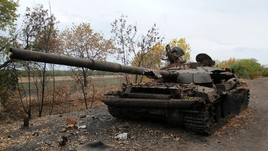 A Ukrainian tank destroyed in recent battles with the Russian troops is seen on a  road near the village of Dmytrivka, Luhansk region in the eastern Ukraine Tuesday, Sept. 23, 2014.  Despite of the declared cease-fire between the separatists and the Ukrainian military in eastern Ukraine occasional shooting has been reported. (AP Photo/Petro Zadorozhnyy)