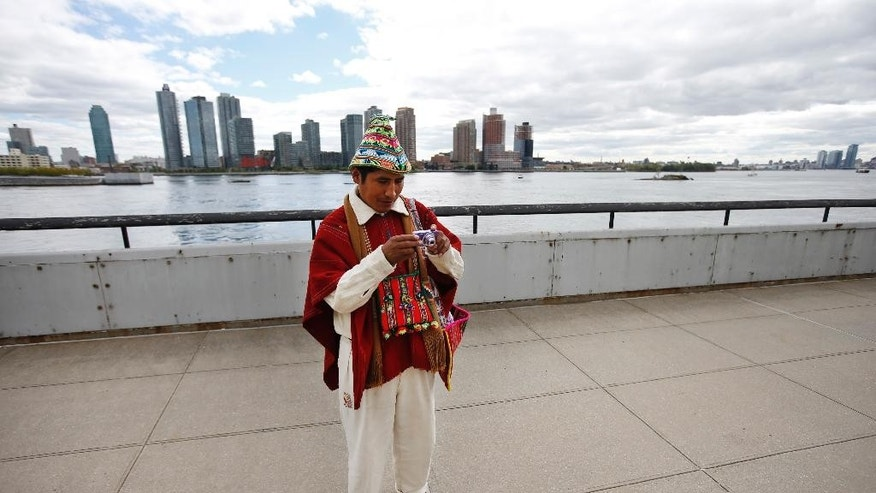 Tomas Mamani, of La Paz, Bolivia, looks at his camera after taking a photo outside United Nations headquarters, Monday, Sept. 22, 2014.  The World Conference on Indigenous Peoples began Monday at the U.N. (AP Photo/Jason DeCrow)