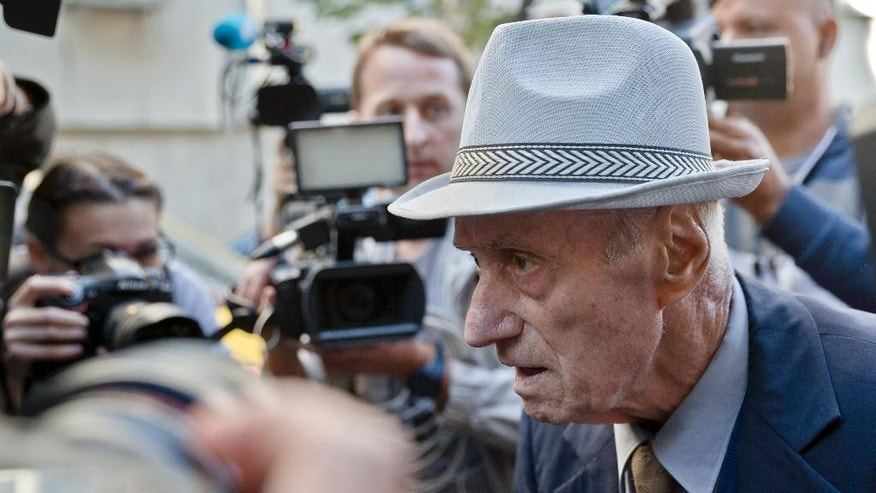 Media surrounds retired Lt. Col. Alexandru Visinescu, who ran the Ramnicu Sarat communist prison from 1956 to 1963 as he leaves a court in Bucharest, Romania, Wednesday, Sept. 24, 2014, after attending the first hearing of a trial in which he is charged with crimes against humanity. Visinescu, who turns 89 this week, told The Associated Press earlier that the court would have to prove his actions led to prisoners' deaths and denied wrongdoing. (AP Photo/Vadim Ghirda)