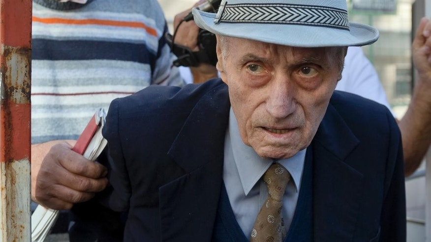 Retired Lt. Col. Alexandru Visinescu, who ran the Ramnicu Sarat communist prison from 1956 to 1963 as he leaves a court in Bucharest, Romania, Wednesday, Sept. 24, 2014, after attending the first hearing of a trial in which he is charged with crimes against humanity. Visinescu, who turns 89 this week, told The Associated Press earlier that the court would have to prove his actions led to prisoners' deaths and denied wrongdoing. (AP Photo/Vadim Ghirda)