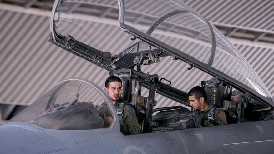 "In this image released Wednesday, Sept. 24, 2014 by the official Saudi Press Agency, Saudi pilots sits in the cockpit of a fighter jet as part of U.S.-led coalition airstrikes on Islamic State militants and other targets in Syria that began early Tuesday. Arab countries' prominent role in initial airstrikes against the Islamic State group in Syria shatters the notion of what a typical American-led military operation looks like and won the Mideast allies' praise from U.S. President Barack Obama for their willingness to stand ""shoulder-to-shoulder"" with the United States. It is a reflection of their growing concern about the threat posed by Islamic extremists, and a chance to flex some military muscle toward regional rival Iran _ a key supporter of governments in both Syria and Iraq. The strategy is not without risks. (AP Photo/Saudi Press Agency)"