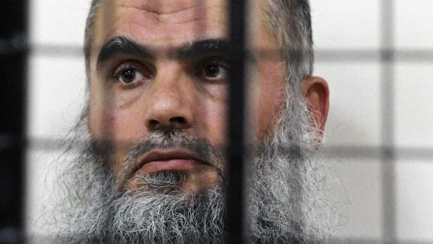 FILE - The radical Al Qaeda-linked preacher Abu Qatada sits behind bars at the Jordanian military court in Amman. (AP Photo/Raad Adayleh, File)