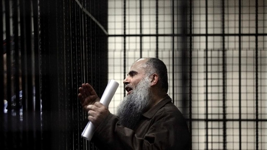 FILE -In this Sunday, Sept. 7, 2014 file photo, radical al-Qaida-linked preacher Abu Qatada speaks to the press prior to his verdict at the Jordanian military court in Amman, Jordan.  On Wednesday, Sept. 24, 2014, a Jordanian military court acquitted Abu Qatada on terrorism charges, for his role in plotting attacks against Americans and Israelis, ruling there was insufficient evidence. The decision was handed down in the case presided over by civilian judges in the Jordanian capital, Amman. (AP Photo/Mohammad Hannon, File)