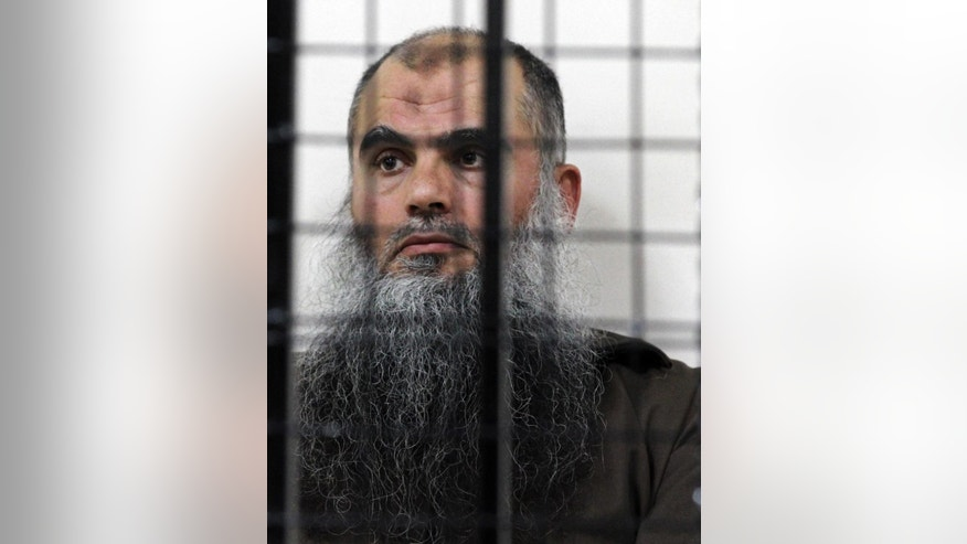 FILE - The radical al-Qaida-linked preacher Abu Qatada sits behind bars at the Jordanian military court in Amman, Jordan, in this, June 26, 2014 file photo. A Jordanian military court acquitted radical Muslim preacher Abu Qatada Wednesday Sept. 24, 2014 on terrorism charges for his role in plotting attacks against Americans and Israelis. The court ruled there was insufficient evidence against Abu Qatada and his defense lawyer, Husein Mubaidin, says he expects his client to be released within hours. (AP Photo/Raad Adayleh, File)