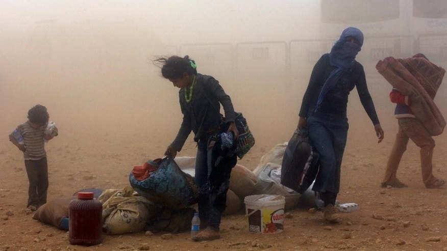 Syrian refugees enter Turkey in a sandstorm at Yumurtalik crossing gate near Suruc, Turkey, Wednesday, Sept. 24, 2014. More than 200,000 people  fleeing the Islamic militants' advance on Kobani, Syria, arrived in Turkey during last five days to find safety.(AP Photo/Burhan Ozbilici)