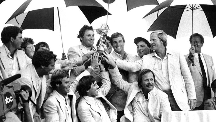 FILE - In this Oct. 17, 1983 file photo, members of the US team pose under umbrellas with the trophy following their narrow one point victory over the European team, in the Ryder Cup golf tournament in Palm Beach Gardens, Fla. After the closest Ryder Cup in years, the US would not win again till 1991. The players include from centre left top, Ray Floyd, Curtis Strange, Lanny Wadkins, and captain Jack Nicklaus. (AP Photo/Eliot Schechter, File)