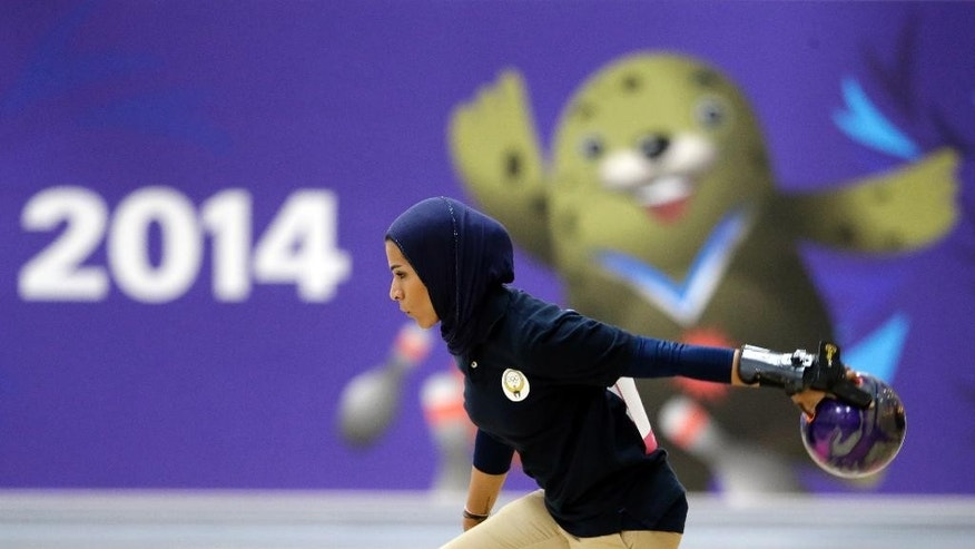 "FILE - IN this Wednesday, Sept. 24, 2014 file photo, Kuwait's Karam Altaf competes in women's singles squad A bowling competition at Anyang Hogye Gymnasium at the 17th Asian Games in Anyang, South Korea. The Qatar women's basketball team forfeited its Asian Games match against Mongolia after players were refused permission to wear a hijab. Incheon Asian Games Organizing Committee spokeswoman Anna Jihyun You told The Associated Press on Wednesday that the players ""had refused to take off the hijab"" and the match was awarded to the opposition. (AP Photo/Lee Jin-man, File)"