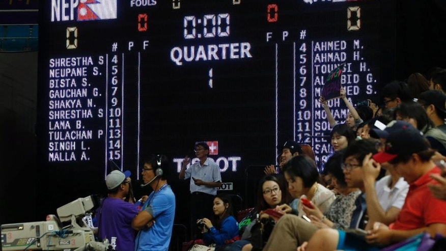 A score board shows the start list of Nepal and Qatar team members for the women's preliminary round basketball match at the 17th Asian Games in Incheon, South Korea, Thursday, Sept. 25, 2014. Qatar's delegation chief says the women's basketball team has withdrawn from the Asian Games after organizers refused to let players wear hijabs in competition. (AP Photo/Kin Cheung)