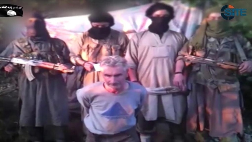 In this still image from video published on the Internet on Wednesday, Sept. 24, 2014, by a group calling itself Jund al-Khilafah, or Soldiers of the Caliphate, members of the group stand behind French mountaineer Herve Gourdel just before beheading him. In the video, the men pledge their allegiance to the leader of the Islamic State group, Abu Bakr al-Baghdadi, before killing Gourdel, 55, who they abducted on Sunday, Sept. 21. (AP Photo)