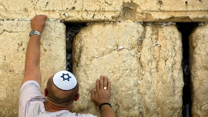 A Jewish man places a note at the Western Wall, the holiest site where Jews can pray, ahead of the Jewish New Year in Jerusalem's old city,  Wednesday, Sept. 24, 2014. People of all faiths slip notes between the stones in the belief that god will answer their prayers.  (AP Photo/Sebastian Scheiner)