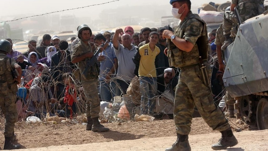 Turkish soldiers stand as Syrian refugees wait for permission to enter Turkey at the Yumurtalik crossing gate near Suruc, Turkey, Wednesday, Sept. 24, 2014. More than 200,000 people  fleeing the Islamic militants' advance on Kobani, Syria, arrived in Turkey during last five days to find safety.(AP Photo/Burhan Ozbilici)