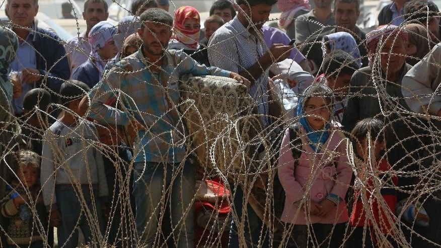 Syrian refugees wait for permission to enter Turkey at Yumurtalik crossing gate near Suruc, Turkey, Wednesday, Sept. 24, 2014. More than 200,000 people fleeing the Islamic militantsí advance on Kobani, Syria, arrived in Turkey during the last five days to find safety.(AP Photo/Burhan Ozbilici)