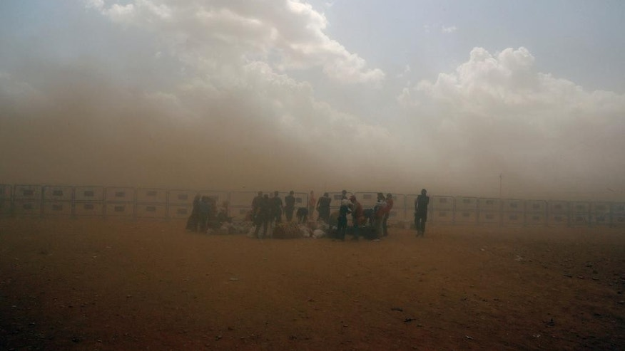 Syrian refugees enter Turkey during a sand storm at Yumurtalik crossing gate near Suruc, Turkey, Wednesday, Sept. 24, 2014. More than 200,000 people  fleeing the Islamic State militantsí advance on Kobani, Syria, arrived in Turkey over the last five days to find safety. (AP Photo/Burhan Ozbilici)