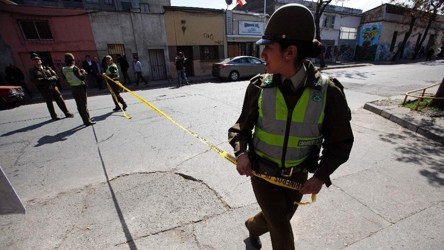 Police tape off an area where a bomb exploded in a residential neighborhood in downtown Santiago, Chile, Thursday, Sept. 25, 2014. The homemade bomb killed a man, officials said, adding to a string of blasts in Chile's capital. (AP Photo/Luis Hidalgo)