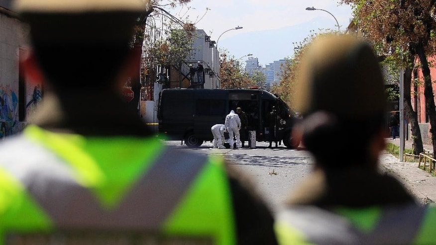 Police forensics inspect an area where a bomb exploded in a residential neighborhood in downtown Santiago, Chile, Thursday, Sept. 25, 2014. The homemade bomb killed a man, officials said, adding to a string of blasts in Chile's capital. (AP Photo/Luis Hidalgo)