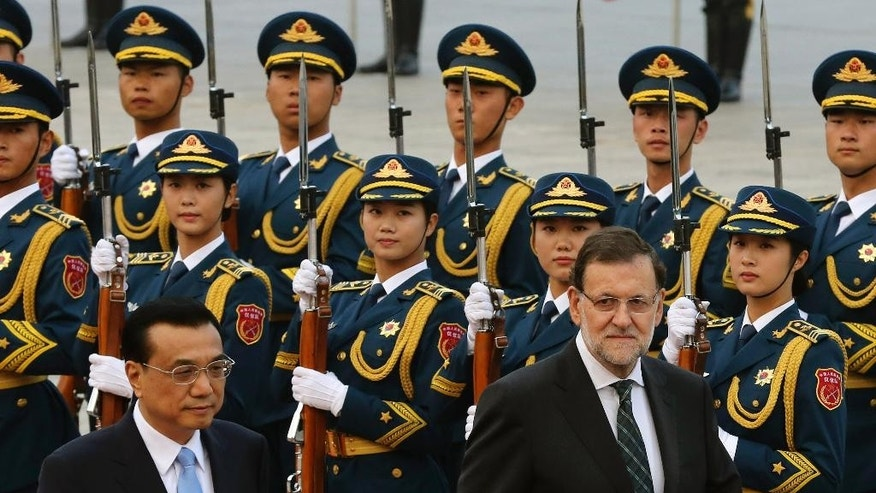 Spain's Prime Minister Mariano Rajoy, right, and Chinese Premier Li Keqiang inspect an honor guard during a welcome ceremony outside the Great Hall of the People in Beijing, China Thursday, Sept. 25, 2014. (AP Photo/Andy Wong)