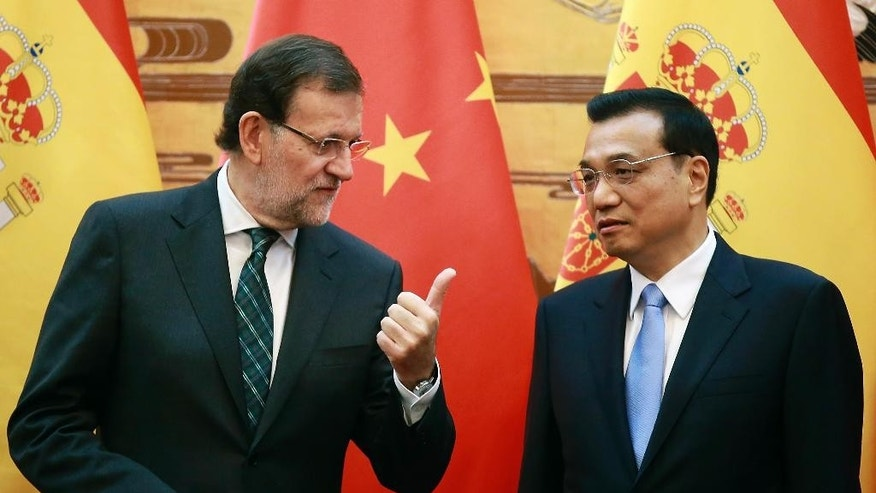 Spanish Prime Minister Mariano Rajoy, left, talks with Chinese Premier Li Keqiang during a signing ceremony between their countries at the Great Hall of the People on Thursday, Sept. 25, 2014, in Beijing, China.  (AP Photo/Feng Li, Pool)