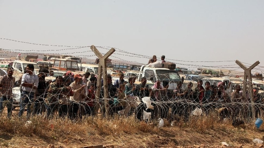 Syrian refugees wait for permission to enter Turkey at Yumurtalik crossing gate near Suruc, Turkey, Wednesday, Sept. 24, 2014. More than 200,000 people  fleeing the Islamic State militants' advance on Kobani, Syria, arrived in Turkey over the last five days to find safety. (AP Photo/Burhan Ozbilici)