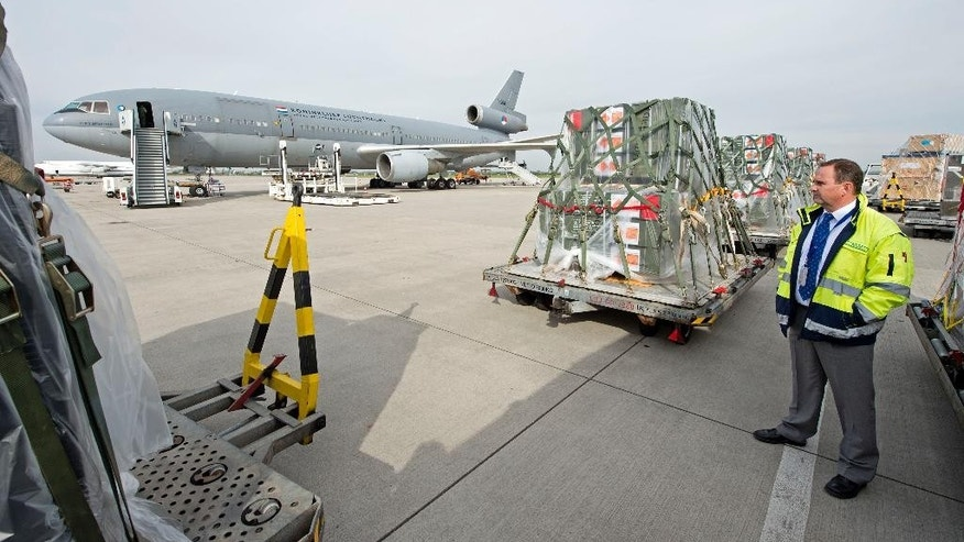A security man stands besides containers with military equipment for Iraq in front of a Dutch air force plane at the airport in Leipzig, central Germany, Wednesday, Sept. 24, 2014. The first German delivery of weapons and ammunition to Iraq had to be postponed due to a technical problem of the Dutch plane. (AP Photo/Jens Meyer)