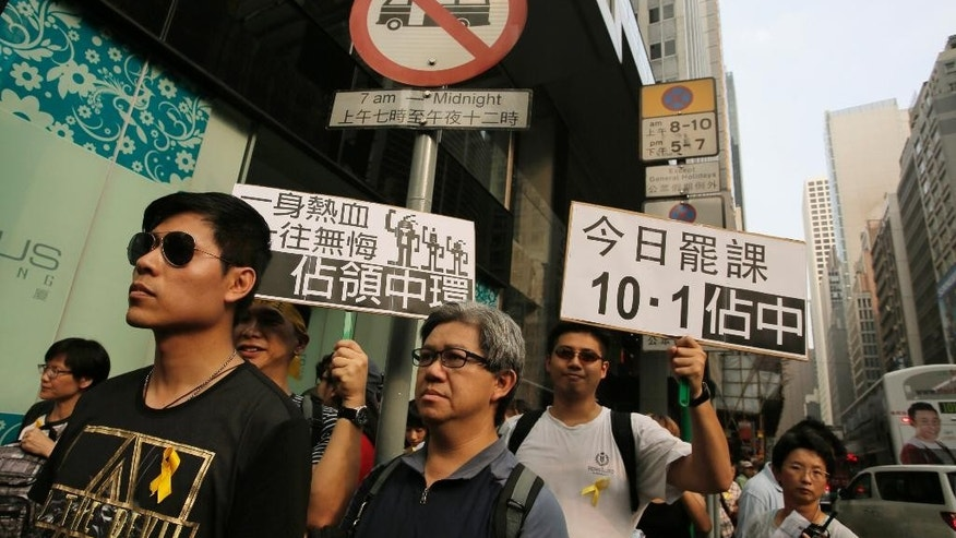 """Protesters raise a placards that read """"Occupy Central"""" at the financial Central district during a protest on the third day of a week-long boycott of classes in Hong Kong, Wednesday, Sept. 24, 2014. Thousands of Hong Kong college and university students boycotted classes to protest Beijing's decision to restrict voting reforms, the start of a weeklong strike that marks the latest phase in the battle for democracy in the southern Chinese city. (AP Photo/Vincent Yu)"""