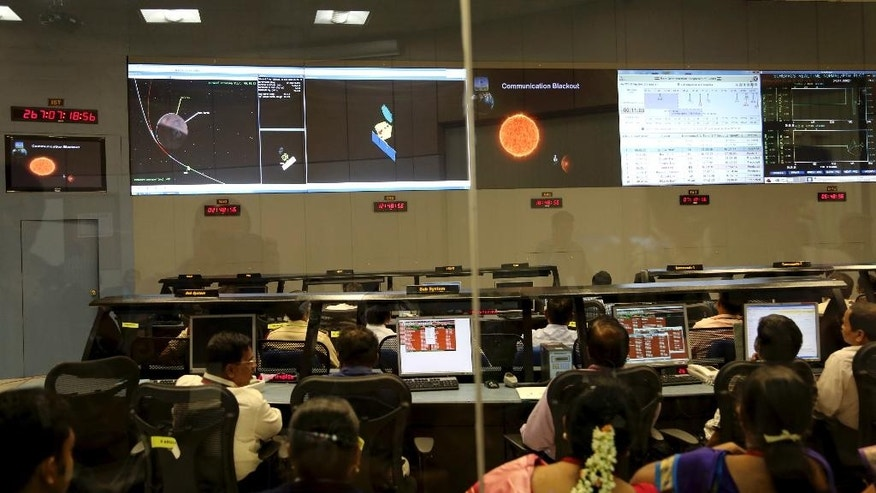 Indian Space Research Organisation scientists watch screens display the graphics explaining Mars Orbiter Mission at their Telemetry, Tracking and Command Network complex in Bangalore, India, Wednesday, Sept. 24, 2014. India triumphed in its first interplanetary mission, placing a satellite into orbit around Mars on Wednesday morning and catapulting the country into an elite club of deep-space explorers. (AP Photo/Aijaz Rahi)