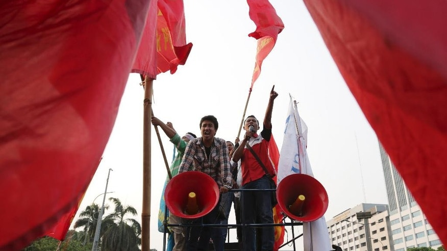 Protesters shout slogans against a regional election bill during a rally in front of the parliament building in Jakarta, Indonesia, Thursday, Sept. 25, 2014. Parliament is holding a plenary session to take decision on the new bill that aimed at returning the authority to organize the country's regional elections to the Regional Legislative Councils. (AP Photo/Achmad Ibrahim)