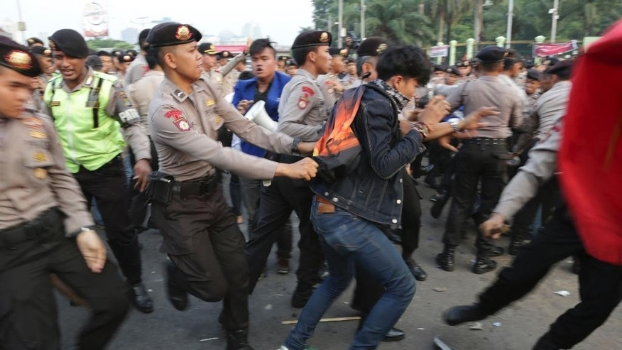 A police officer drags a protester during a rally, opposing a regional election bill in front of the parliament building in Jakarta, Indonesia, Thursday, Sept. 25, 2014. Parliament is holding a plenary session to take decision on the new bill that aimed at returning the authority to organize the country's regional elections to the Regional Legislative Councils. (AP Photo/Achmad Ibrahim)