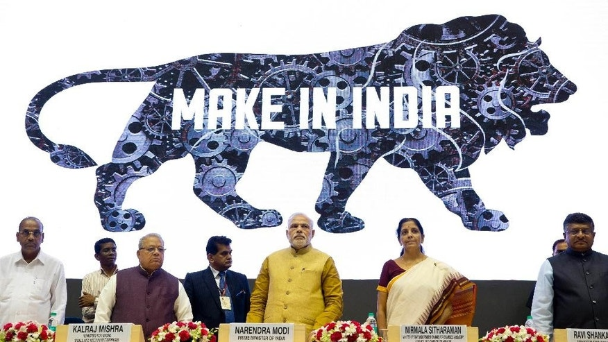 Indian Prime Minister Narendra Modi, center, unveils the logo of 'Make in India' initiative in New Delhi, India, Thursday, Sept. 25, 2014. Scores of business leaders from India and abroad attended the launch of the initiative where in the Indian Prime Minister called on manufacturers across the globe to come and make India a manufacturing hub. (AP Photo/Saurabh Das)