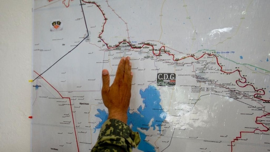 In this Sept. 5, 2014 photo, a soldier points out the border area, shared by the states of Texas and Tamaulipas, under gang influence on a map at a military base in Ciudad Mier, Tamaulipas state, Mexico. As Mexico prepares to develop rich shale fields along the Gulf Coast, and attract foreign investors, the country will be challenged to tame the brutal drug cartels that rule the region and steal billions of dollars' worth of oil from pipelines. (AP Photo/Eduardo Verdugo)