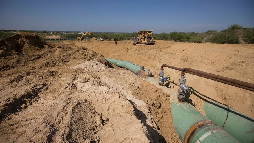 In this Sept. 7, 2014 photo, new pipelines that will carry gas from Texas to Mexico, eventually reaching the city of Guanajuato, are laid underground near General Bravo, in Nuevo Leon state, Mexico. So far this year, thieves across Mexico have drilled so many illegal taps into state-owned pipelines, siphoning off  gas and oil, that they're on pace to set a new annual record. (AP Photo/Eduardo Verdugo)