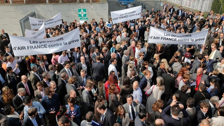 Air France workers gather in front of the company headquarters as they demonstrate against the pilots strike, in Roissy, outside Paris, Wednesday, Sept. 24, 2014. Air France-KLM says it isn't ready to abandon a plan to transfer activities to a low-cost carrier, contradicting a government minister's claim. France's junior minister for transport, Alain Vidalies, said on RMC radio Wednesday that Air France was withdrawing the plan in the face a protracted strike by pilots. Banners read, 'Air France workers against the strike'. (AP Photo/Christophe Ena)