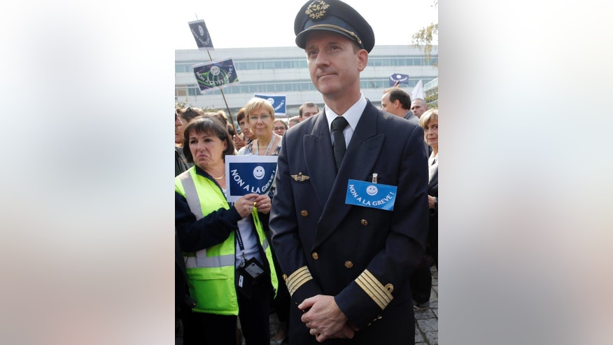 A pilot and Air France workers gather in front of the company headquarters as they  demonstrate against the pilots strike, in Roissy, outside Paris, Wednesday, Sept. 24, 2014. Air France-KLM says it isn't ready to abandon a plan to transfer activities to a low-cost carrier, contradicting a government minister's claim. France's junior minister for transport, Alain Vidalies, said on RMC radio Wednesday that Air France was withdrawing the plan in the face a protracted strike by pilots. Posters read, 'No to this strike'. (AP Photo/Christophe Ena)