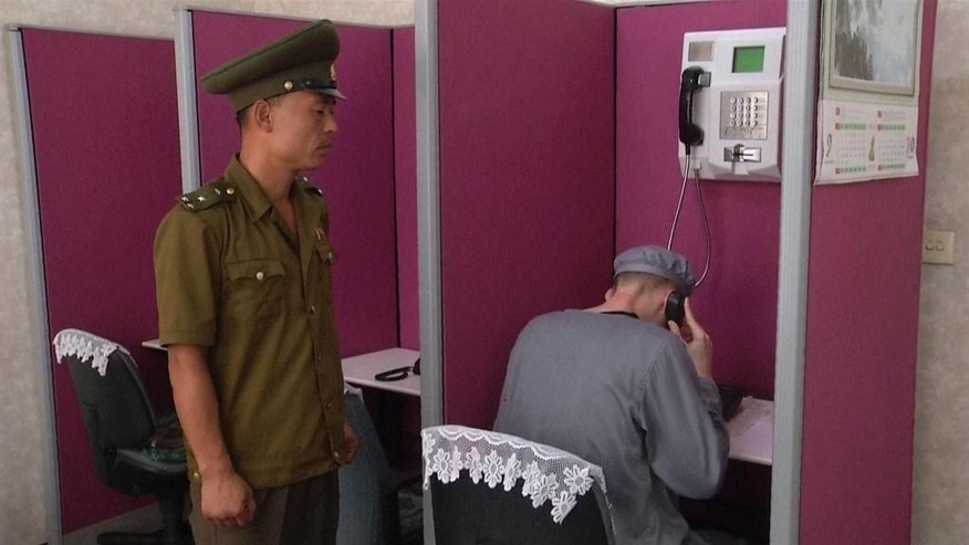 In this Wednesday, Sept. 24, 2014 photo from a video shot by a North Korean TV crew employed locally by AP Television News, Matthew Miller, an American man recently sentenced by North Korea to six years of hard labor, makes a phone call in Pyongyang, North Korea. Under close guard and with only enough time to respond to one question, Miller spoke briefly to an Associated Press Television News journalist at a Pyongyang hotel, where he had been brought to make a phone call to his family. It was his first appearance since he was convicted Sept. 14 of entering the country illegally to commit espionage. (AP Photo/APTN)