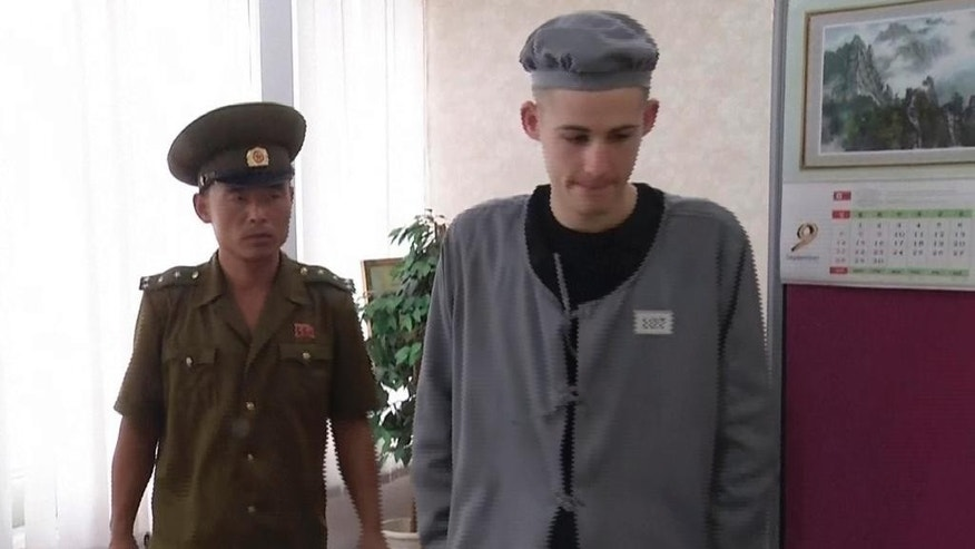 In this Wednesday, Sept. 24, 2014 photo from a video shot by a North Korean TV crew employed locally by AP Television News, Matthew Miller, an American man recently sentenced by North Korea to six years of hard labor, walks away after making a phone call in Pyongyang, North Korea. Under close guard and with only enough time to respond to one question, Miller spoke briefly to an Associated Press Television News journalist at a Pyongyang hotel, where he had been brought to make a phone call to his family. It was his first appearance since he was convicted Sept. 14 of entering the country illegally to commit espionage. (AP Photo/APTN)