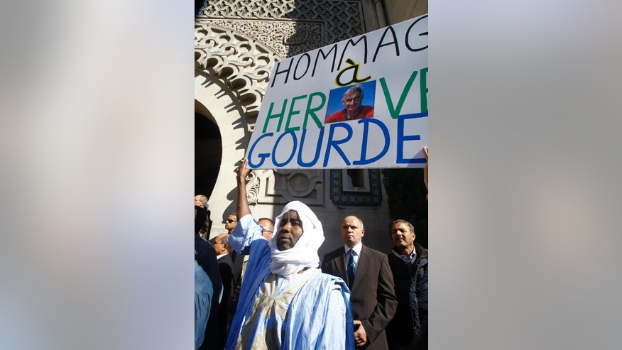 A Muslim from Mauritania pays homage to French mountaineer Hervé Gourdel, his photo in the centre of the banner, who was beheaded by Islamist militants in Algeria, during a gathering in front of the Paris Grand Mosque, Friday Sept. 26, 2014.  The gathering was part of demonstrations by French Muslims against the killings happening in the name of their religion. (AP Photo/Remy de la Mauviniere)