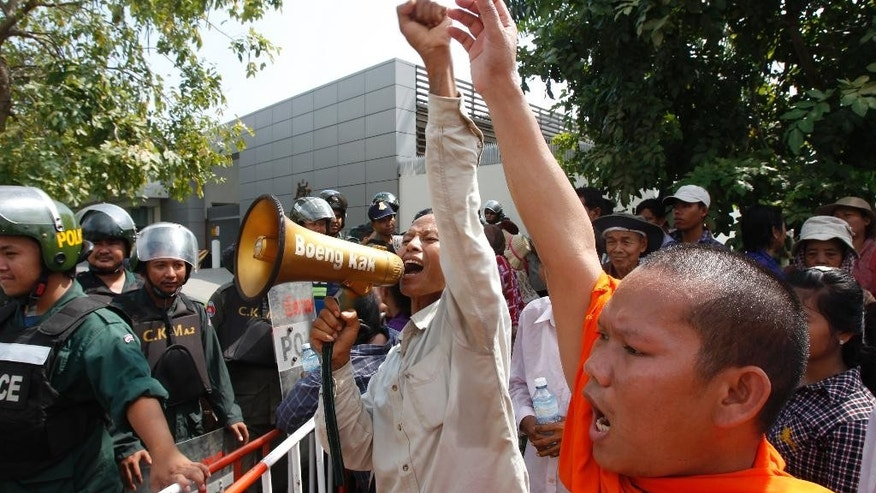 A Cambodian Buddhist monk, right, and a villager, center, shout slogans during a protest near the Australian Embassy in Phnom Penh, Cambodia, Friday, Sept. 26, 2014.  About 100 people, including Buddhist monks, have protested outside of Australia's embassy in Cambodia against a deal to be signed late Friday that will see asylum-seekers rejected by Australia resettle in Cambodia.  (AP Photo/Heng Sinith)