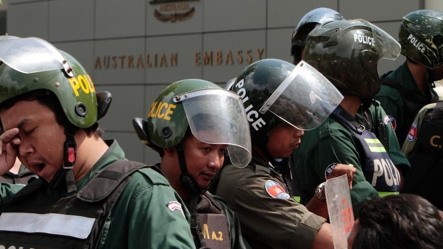Cambodian riot police officers stand guard in front of Australian Embassy in Phnom Penh, Cambodia Friday, Sept. 26, 2014. About 100 people, including Buddhist monks, have protested outside of Australia's embassy in Cambodia against a deal to be signed later Friday that will see asylum-seekers rejected by Australia resettle in Cambodia. (AP Photo/Heng Sinith)