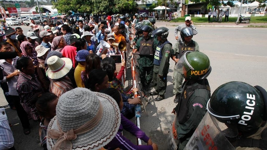 Cambodian protesters are blocked on a street near Australian Embassy in Phnom Penh, Cambodia, Friday, Sept. 26, 2014. About 100 people, including Buddhist monks, have protested outside of Australia's embassy in Cambodia against a deal to be signed later Friday that will see asylum-seekers rejected by Australia resettle in Cambodia. (AP Photo/Heng Sinith)