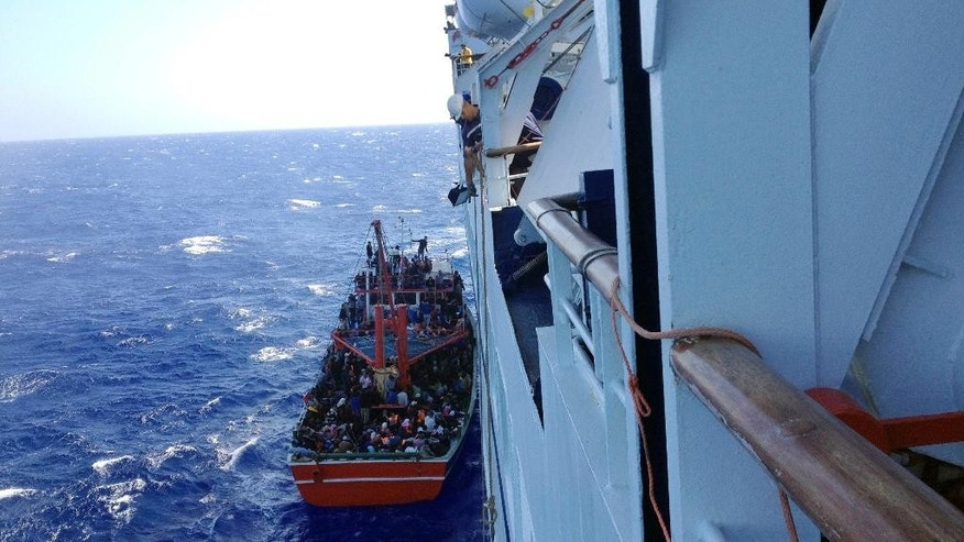 This Thursday, Sept. 25, 2014 photo taken from a cruise ship that rescued the migrants from a small boat stranded off the east Mediterranean island's main Limassol port, Cyprus, shows apparent refugees on the boat. More than 300 people, apparent refugees fleeing from Syria, refused to leave the cruise ship, a cruise line official said Thursday.(AP Photo/Haris Milonas)